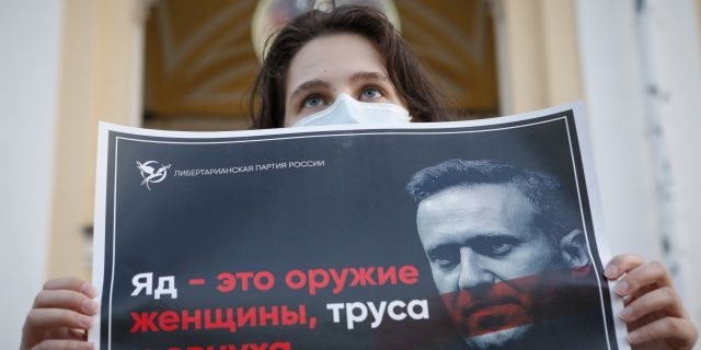 """A protester stands holds a poster reads """"poison is the weapon of a woman, a coward and a eunuch!"""" during a picket in support of Russian opposition leader Alexei Navalny in the center of St. Petersburg, Russia, Thursday, Aug. 20, 2020. (AP Photo/Elena Ignatyeva)"""