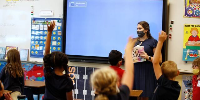 Students raise their hands while a teacher wears a protective mask during a lesson at a public charter school in Provo, Utah, U.S., Aug. 20, 2020. (Getty Images)