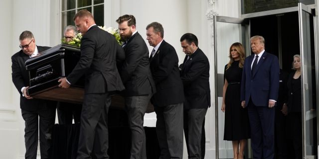 President Donald Trump and first lady Melania Trump hold hands as they watch people carry the casket of Robert Trump out of the White House after a memorial service for the president's younger brother on Friday, Aug 21, 2020, in Washington. (AP Photo/Evan Vucci)