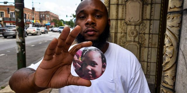 Nathan Wallace stands outside of his home holding a button showing his daughter, Natalia Wallace. Natalia, 7, was killed on the west side of Chicago on July 4. (AP Photo/Matt Marton)