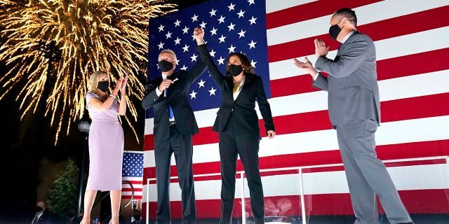 Democratic presidential candidate former Vice President Joe Biden, with Democratic vice presidential candidate Sen. Kamala Harris, D-Calif., raise their arms up as fireworks go off in the background during the fourth day of the Democratic National Convention, Thursday, Aug. 20, 2020, at the Chase Center in Wilmington, Del. Looking on are Jill Biden, far left, and Harris' husband Doug Emhoff, far right. (AP Photo/Andrew Harnik)