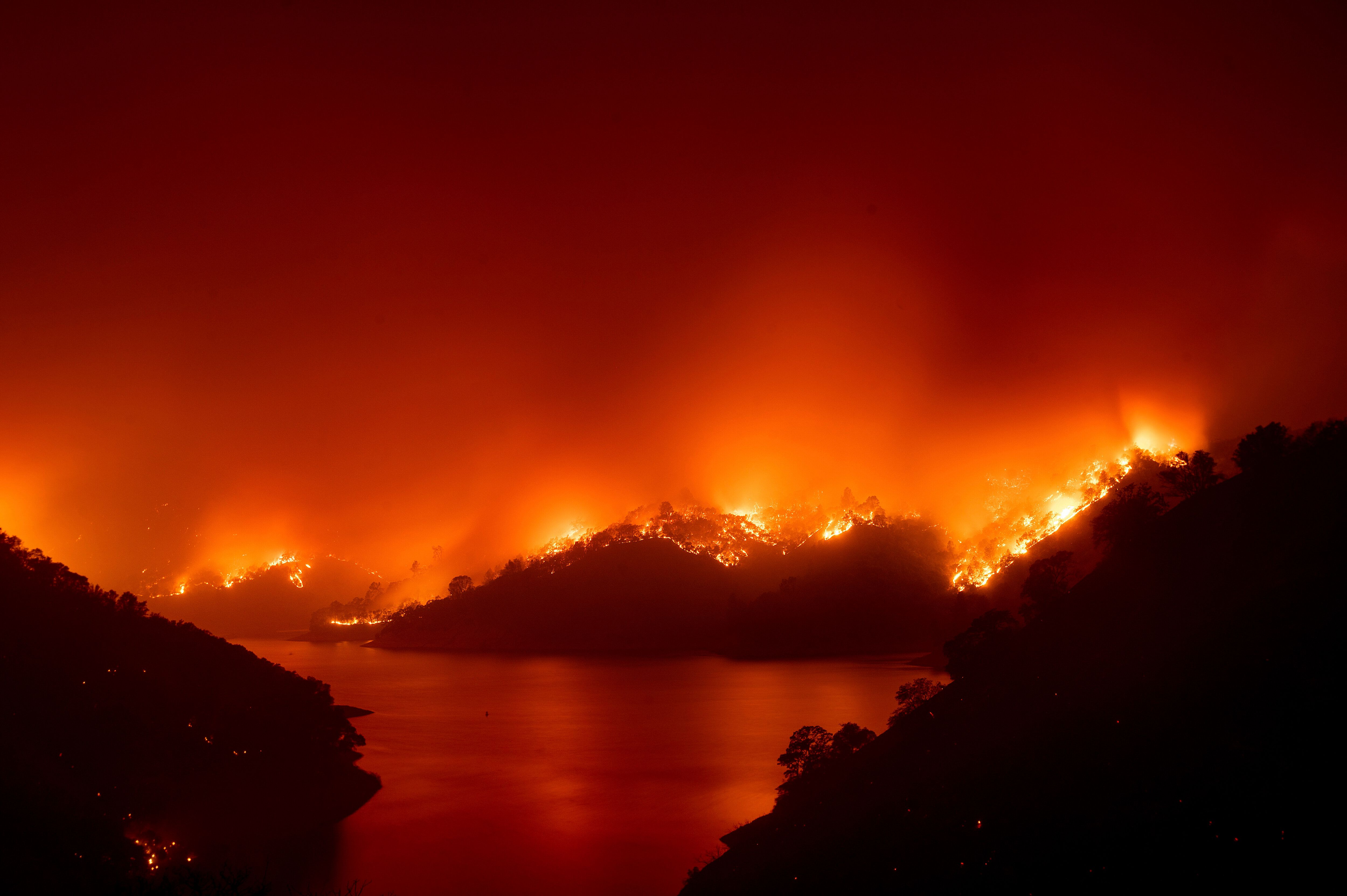 Flames from the wildfire designated as the LNU Lightning Complex are seen around Lake Berryessa in Napa County, California on
