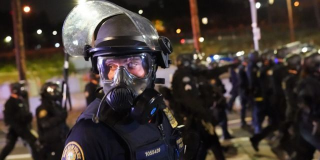 ​​​​​​​A Portland, Ore., police officer scans the crowd while dispersing protesters, Aug. 21, 2020. (Getty Images)