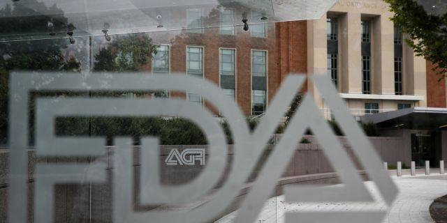 The U.S. Food and Drug Administration building behind FDA logos at a bus stop on the agency's campus in Silver Spring, Md. Aug. 2, 2018. (AP Photo/Jacquelyn Martin, File)