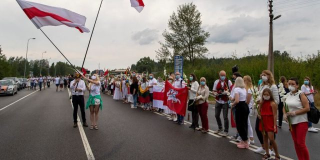 """Supporters of Belarus opposition from Lithuania hold and wave historical Belarusian flags during the """"Freedom Way"""", a human chain of about 50,000 strong from Vilnius to the Belarusian border, near Medininkai, Lithuanian-Belarusian border crossing east of Vilnius, Lithuania, Sunday, Aug. 23, 2020. In Aug. 23, 1989, around 2 million Lithuanians, Latvians, and Estonians joined forces in a living 600 km (375 mile) long human chain Baltic Way, thus demonstrating their desire to be free. Now, Lithuania is expressing solidarity with the people of Belarus, who are fighting for freedom today. (AP Photo/Mindaugas Kulbis)"""