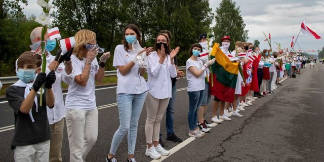 """Supporters of Belarus opposition from Lithuania hold and wave historical Belarusian flags during the """"Freedom Way"""", a human chain of about 50,000 strong from Vilnius to the Belarusian border, during a protest near Medininkai, Lithuanian-Belarusian border crossing east of Vilnius, Lithuania, Sunday, Aug. 23, 2020. In Aug. 23, 1989, around 2 million Lithuanians, Latvians, and Estonians joined forces in a living 600 km (375 mile) long human chain Baltic Way, thus demonstrating their desire to be free. Now, Lithuania is expressing solidarity with the people of Belarus, who are fighting for freedom today. (AP Photo/Mindaugas Kulbis)"""