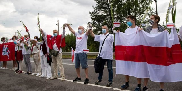 """People hold hands, historical white-red-white flags of Belarus and flowers as they participate in a """"Freedom Way"""", a human chain of about 50,000 strong from Vilnius to the Belarusian border, during a protest near Medininkai, Lithuanian-Belarusian border crossing east of Vilnius, Lithuania, Sunday, Aug. 23, 2020. In Aug. 23, 1989, around 2 million Lithuanians, Latvians, and Estonians joined forces in a living 600 km (375 mile) long human chain Baltic Way, thus demonstrating their desire to be free. Now, Lithuania is expressing solidarity with the people of Belarus, who are fighting for freedom today. (AP Photo/Mindaugas Kulbis)"""