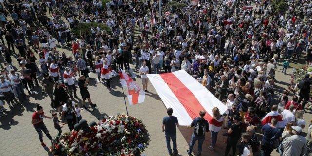People hold an old Belarusian National flag and gather at the place where Alexander Taraikovsky died amid the clashes protesting the election results, during his civil funeral in Minsk, Belarus, Saturday, Aug. 15, 2020. Taraikovsky died Monday as demonstrators roiled the streets of the capital Minsk, denouncing official figures showing that authoritarian President Alexander Lukashenko, in power since 1994, had won a sixth term in office. (AP Photo/Dmitri Lovetsky)