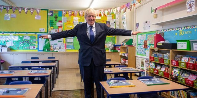 """FILE - In this Aug. 10, 2020, file photo, Britain's Prime Minister Boris Johnson visits St Joseph's Catholic Primary School, London, to see the steps they are taking to be COVID-secure ahead of children returning in September. Britain's prime minister is asking parents to set aside their fears and send their children back to school next month when the nation's schools fully reopen for the first time since the coronavirus pandemic shut then down more than five months ago. Johnson said it was the government's """"moral duty'' to reopen the schools as he stressed that authorities now know more about COVID-19 than they did when the country went into lockdown on March 23. (Lucy Young/Pool via AP, File)"""