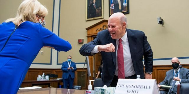 DeJoy elbow bumps with Rep. Carolyn Maloney, D-N.Y., the chair of the Oversight Committee, before a House Oversight and Reform Committee hearing, Aug. 24, 2020, in Washington. (Tom Williams/Pool via AP)