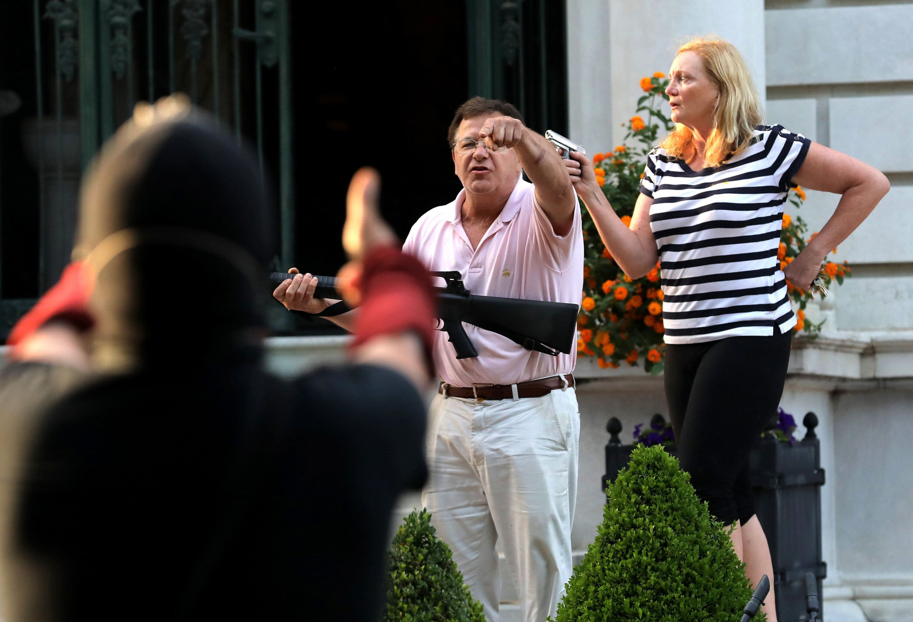 Armed homeowners Mark and Patricia McCloskey stand in front of their house as they confront protesters, June 28, 2020, in the