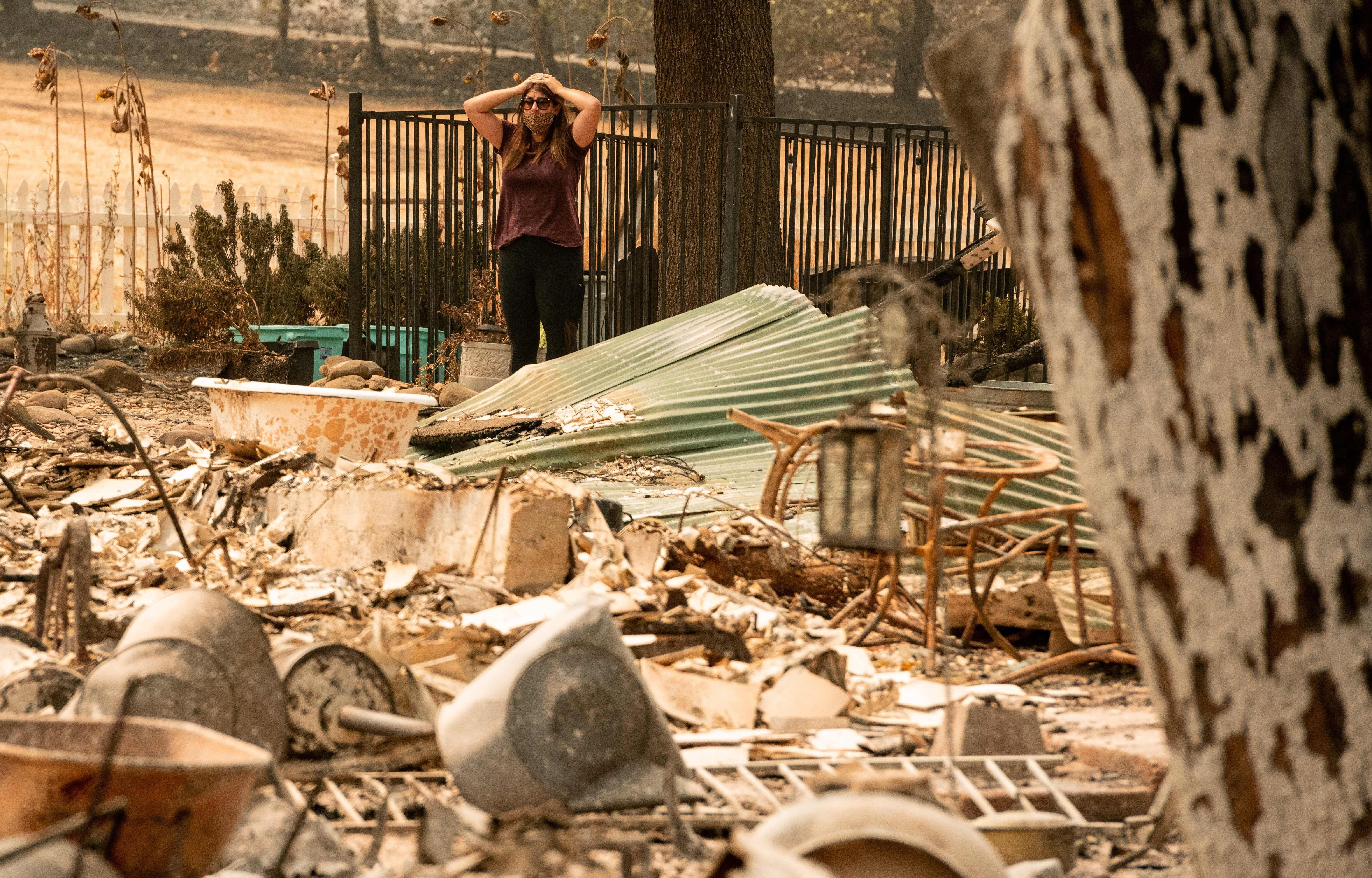 Alyssa Medina reacts to the charred remains of her family home, burned by the LNU Lightning Complex fire in Vacaville, Califo