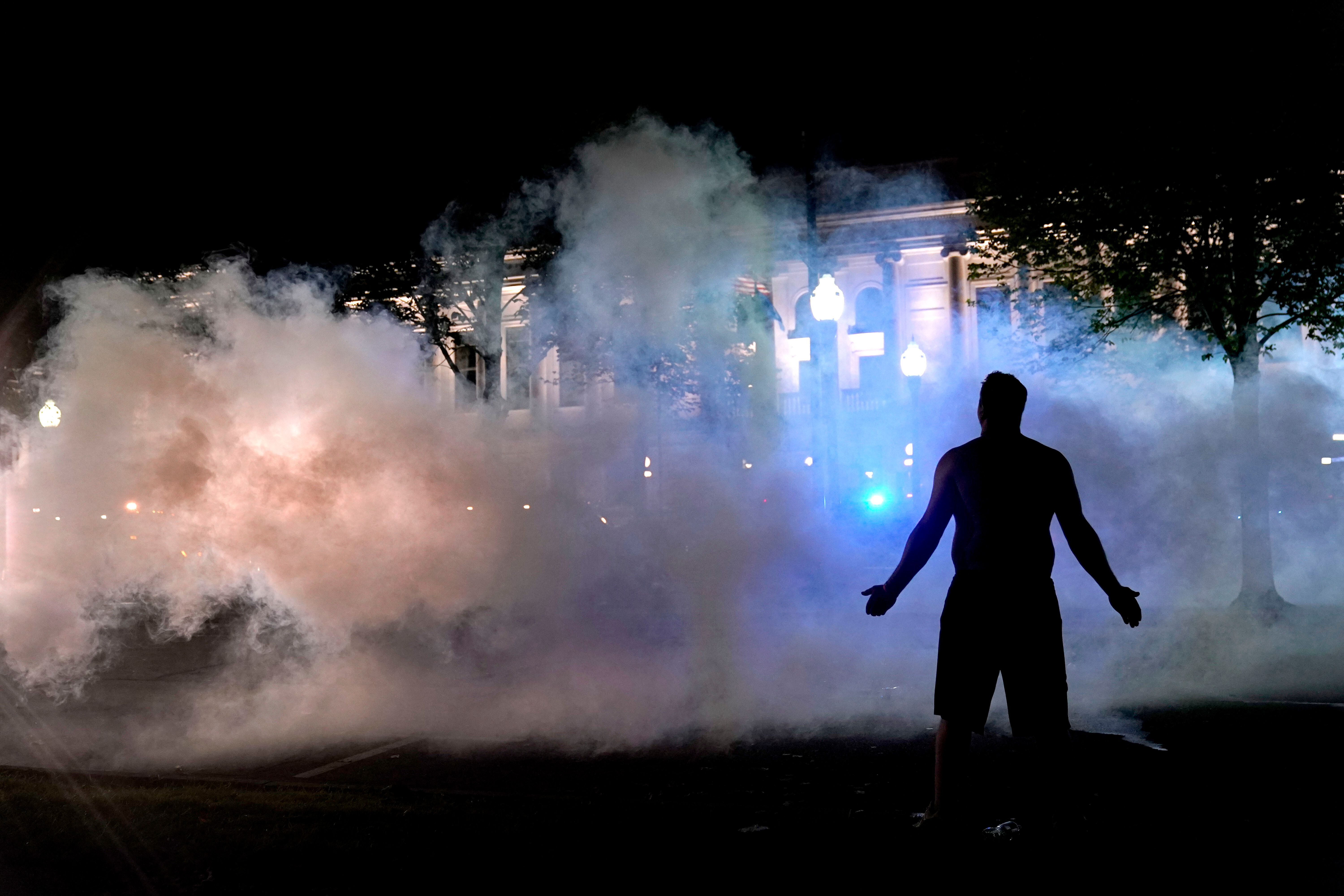 A protester attempts to continue standing through a cloud of tear gas fired by police outside the Kenosha County Courthouse,