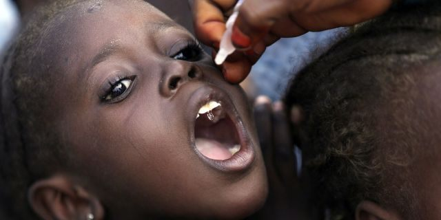 In this Sunday, Aug. 28, 2016, file photo, a health official administers a polio vaccine to a child at a camp for people displaced by Islamist Extremists in Maiduguri, Nigeria. Health authorities on Tuesday, Aug. 25, 2020, are expected to declare the African continent free of the wild poliovirus after decades of effort, though cases of vaccine-derived polio are still sparking outbreaks of the paralyzing disease in more than a dozen countries.