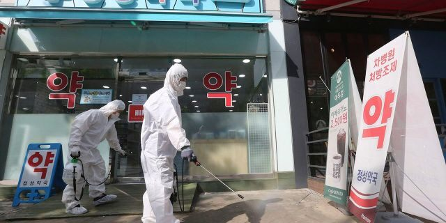 Workers disinfect as a precaution against the coronavirus in front of a pharmacy in Goyang, South Korea, Tuesday, Aug. 25, 2020. South Korea is closing schools and switching back to remote learning in the greater capital area as the country counted its 12th straight day of triple-digit daily increases in coronavirus cases. (AP Photo/Ahn Young-joon)
