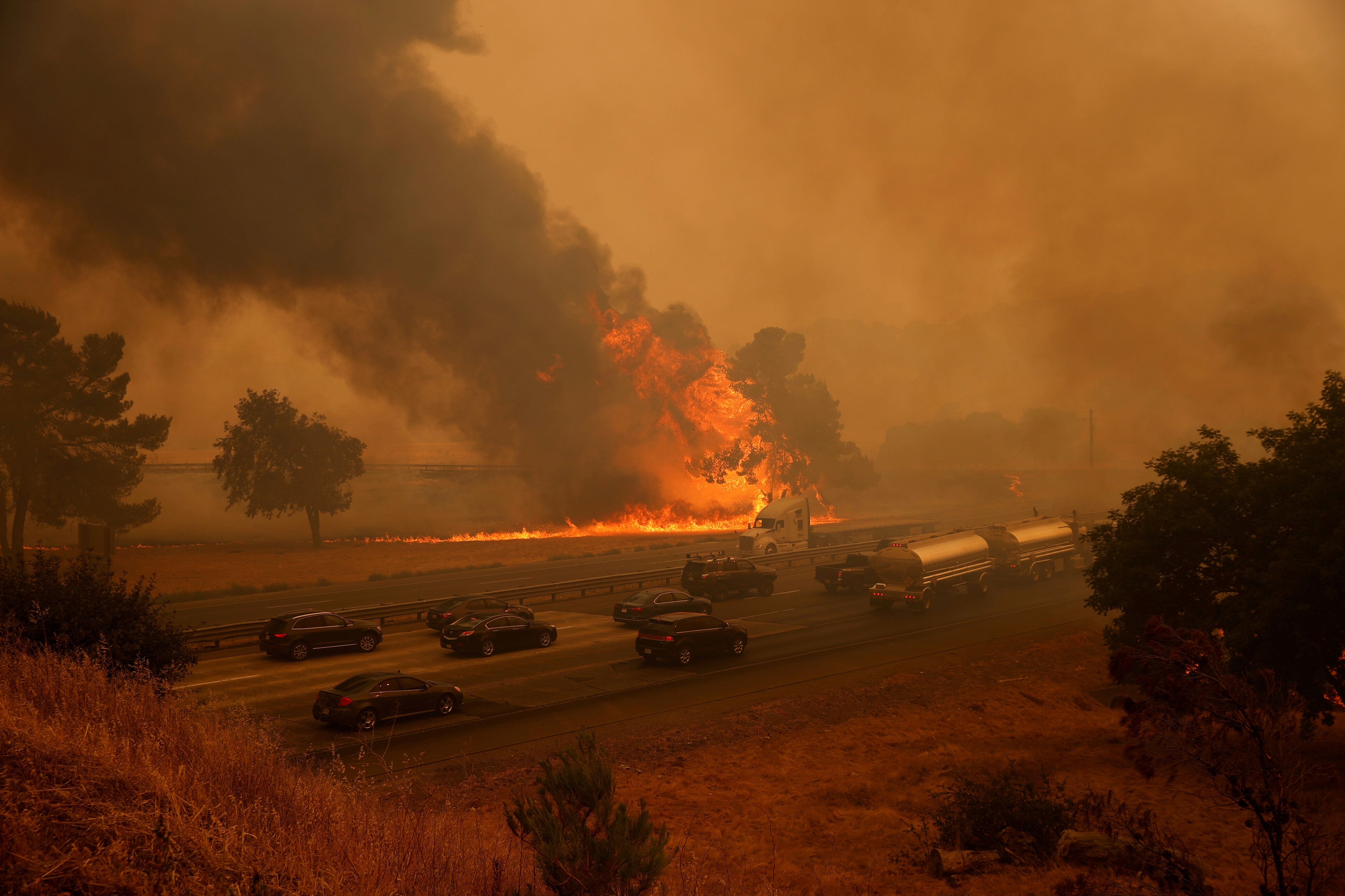 Vehicles drive along Interstate 80 as flames from the LNU Lightning Complex Fire rage on the outskirts of Vacaville, Californ