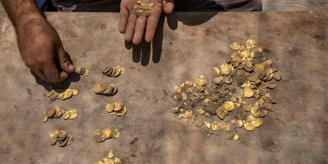 """Israeli archaeologist Shahar Krispin counts gold coins buried in a pottery vessel that was discovered at an archeological site in central Israel, Tuesday, Aug 18, 2020. Israeli archaeologists have announced the discovery of a trove of early Islamic gold coins during recent salvage excavations near the central city of Yavn Tel Aviv. The collection of 425 complete gold coins, most dating to the Abbasid period around 1,100 years ago, is a """"extremely rare"""" find. (AP Photo/Sipa Press, Heidi Levine, Pool)"""