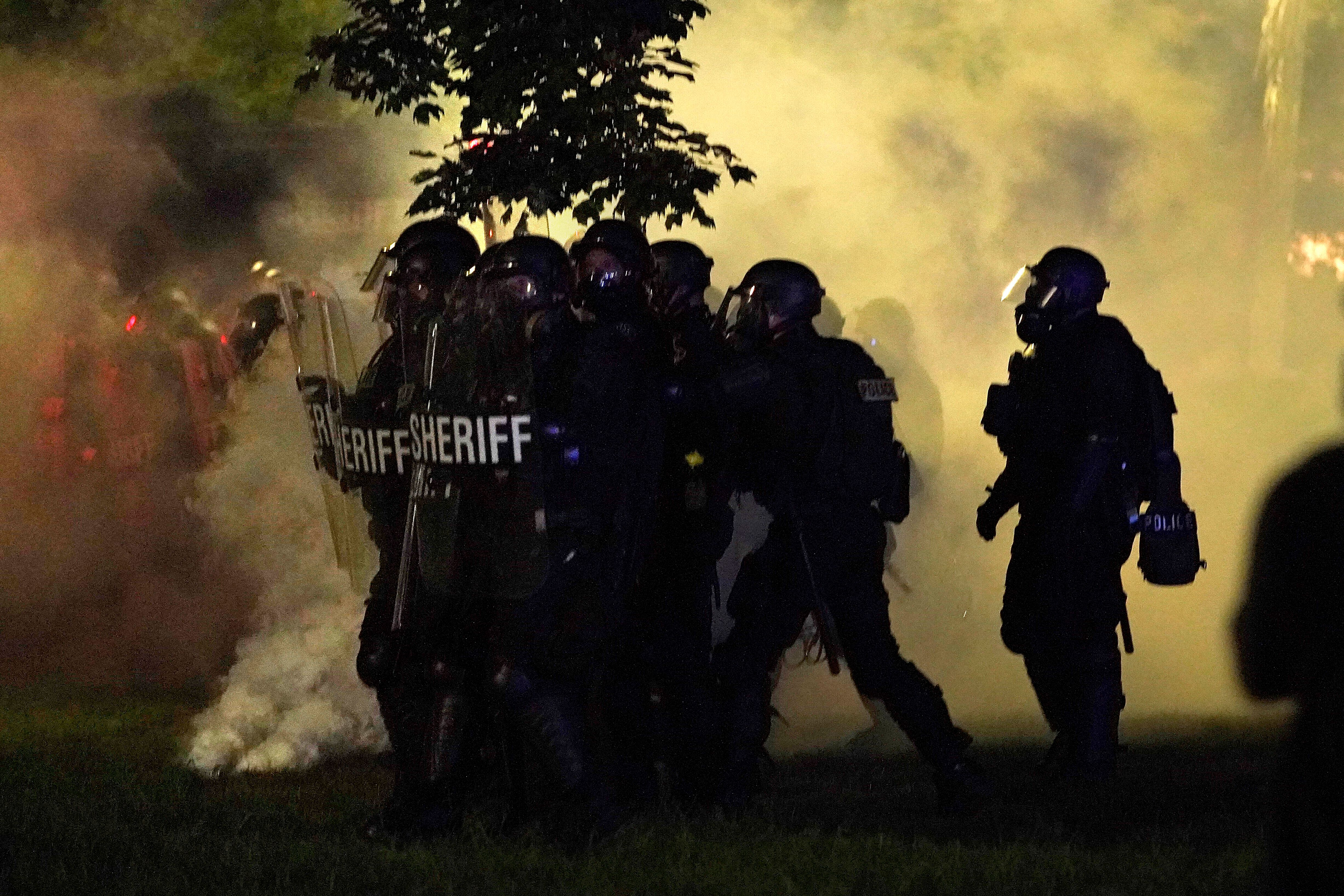 Police in riot gear clear a park during clashes with protesters outside the Kenosha County Courthouse late Tuesday.