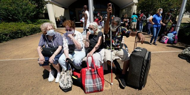 Evacuees, from right to left, Tommie McNeil, Elisabeth Pelham, Nota Norris, and a woman who did not want to be identified, wait to board a bus as they evacuate, Tuesday, Aug. 25, 2020, in Galveston, Texas.
