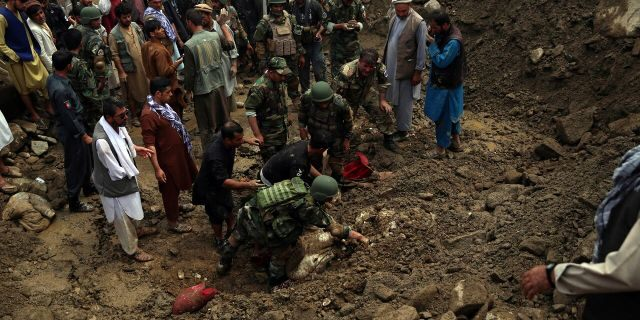 Soldiers and civilians search for bodies after a mudslide caused by heavy flooding, in Parwan province, north of Kabul, Afghanistan, Wednesday, Aug. 26, 2020.