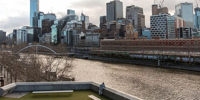A lone man looks out toward the Yarra River and the empty Central Business District during lockdown in Melbourne, the captial city of Victoria state in Australia, on Aug. 5. Victoria state is considered a COVID-19 hotspot and has taken strict measures to prevent the spread of the virus. (AP Photo/Asanka Brendon Ratnayake)