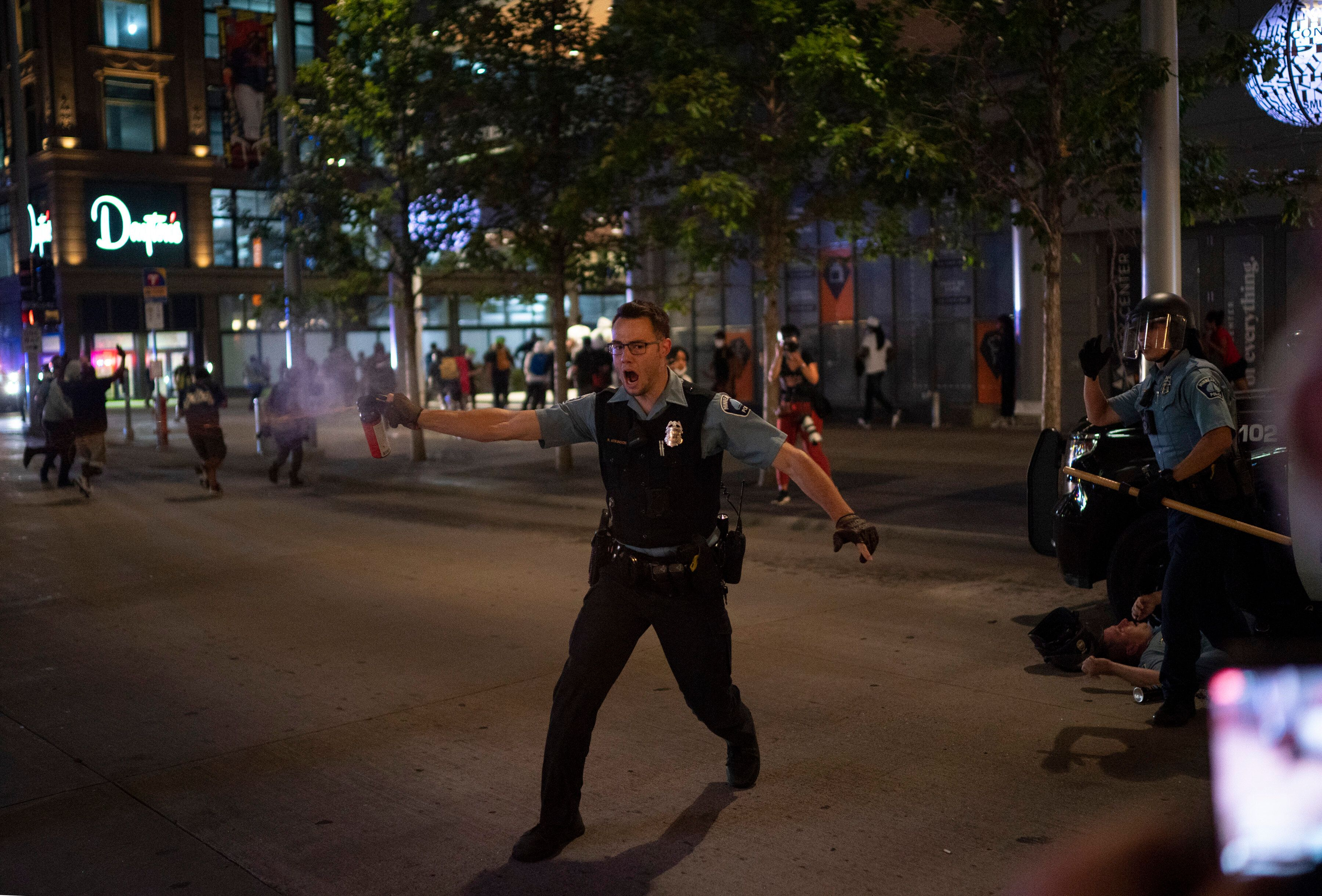 Police spray a substance to clear the area where a colleague was injured on the Nicollet Mall Wednesday in Minneapolis.