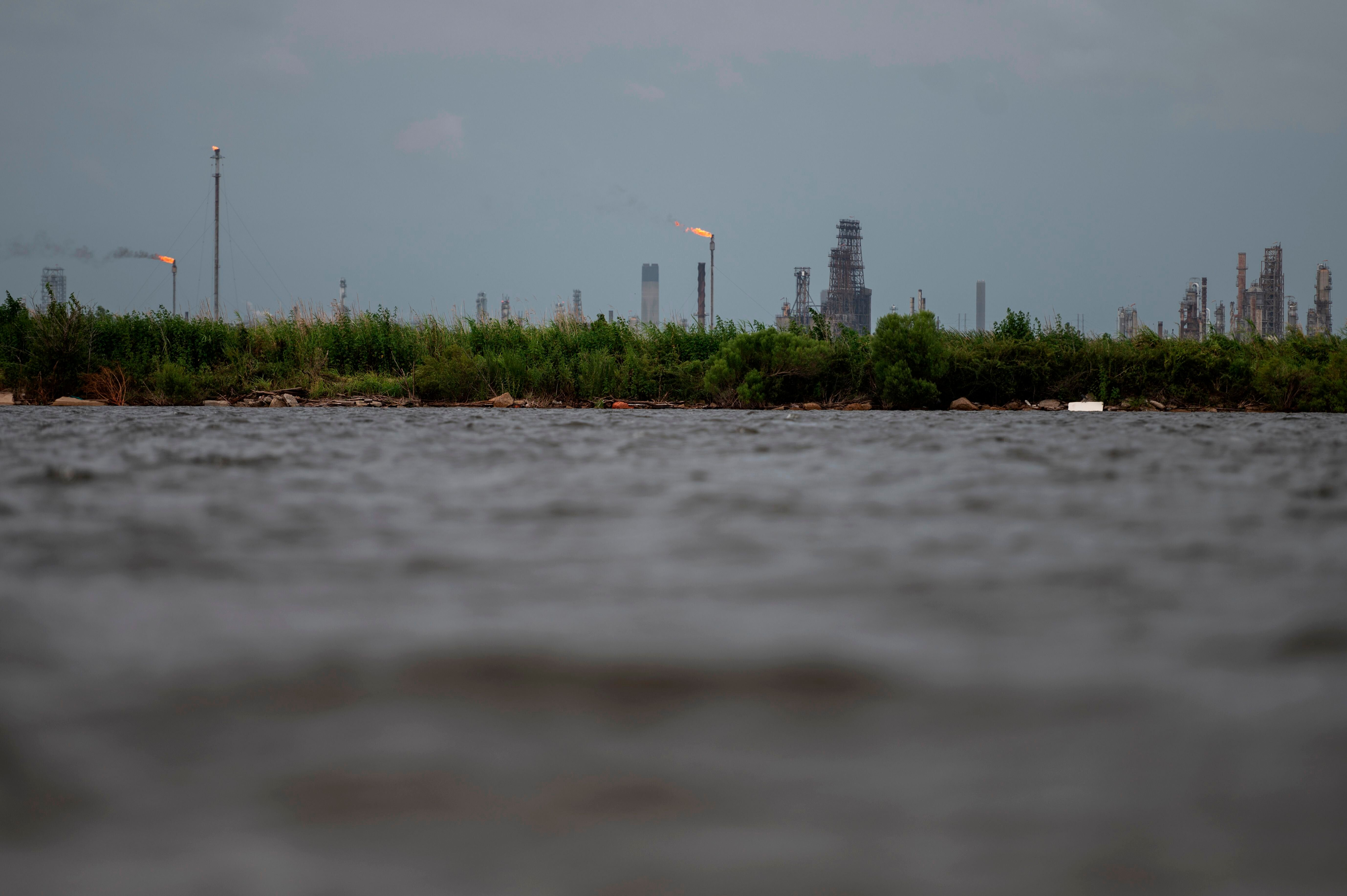 An oil and gas plant is seen across the Bayou Contraband as the water starts to rise before the arrival of Hurricane Laura in