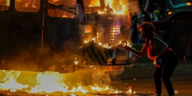 A protester lights a cigarette on a garbage truck that was set on fire during protests late Aug. 24, in Kenosha, Wis., sparked by the shooting of Jacob Blake by a Kenosha Police officer a day earlier. (AP Photo/Morry Gash)