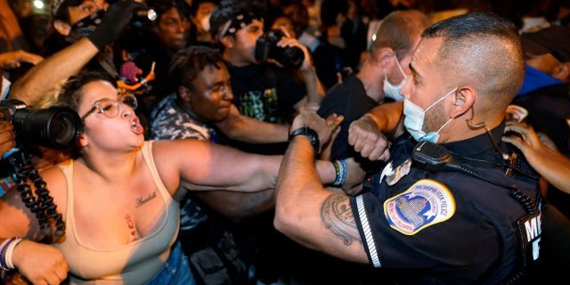 Metropolitan Police are confronted by protestors as police carry away a handcuffed protester along a section of 16th Street, Northwest, renamed Black Lives Matter Plaza, Thursday night, Aug. 27, 2020, in Washington, D.C., after President Donald Trump had finished delivering his acceptance speech from the White House South Lawn. (AP Photo/Julio Cortez)