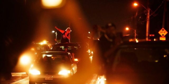 A person in a car raises her fist in solidarity with a march protesting the Sunday police shooting of Jacob Blake, in Kenosha, Wis., on Wednesday. (AP Photo/David Goldman)