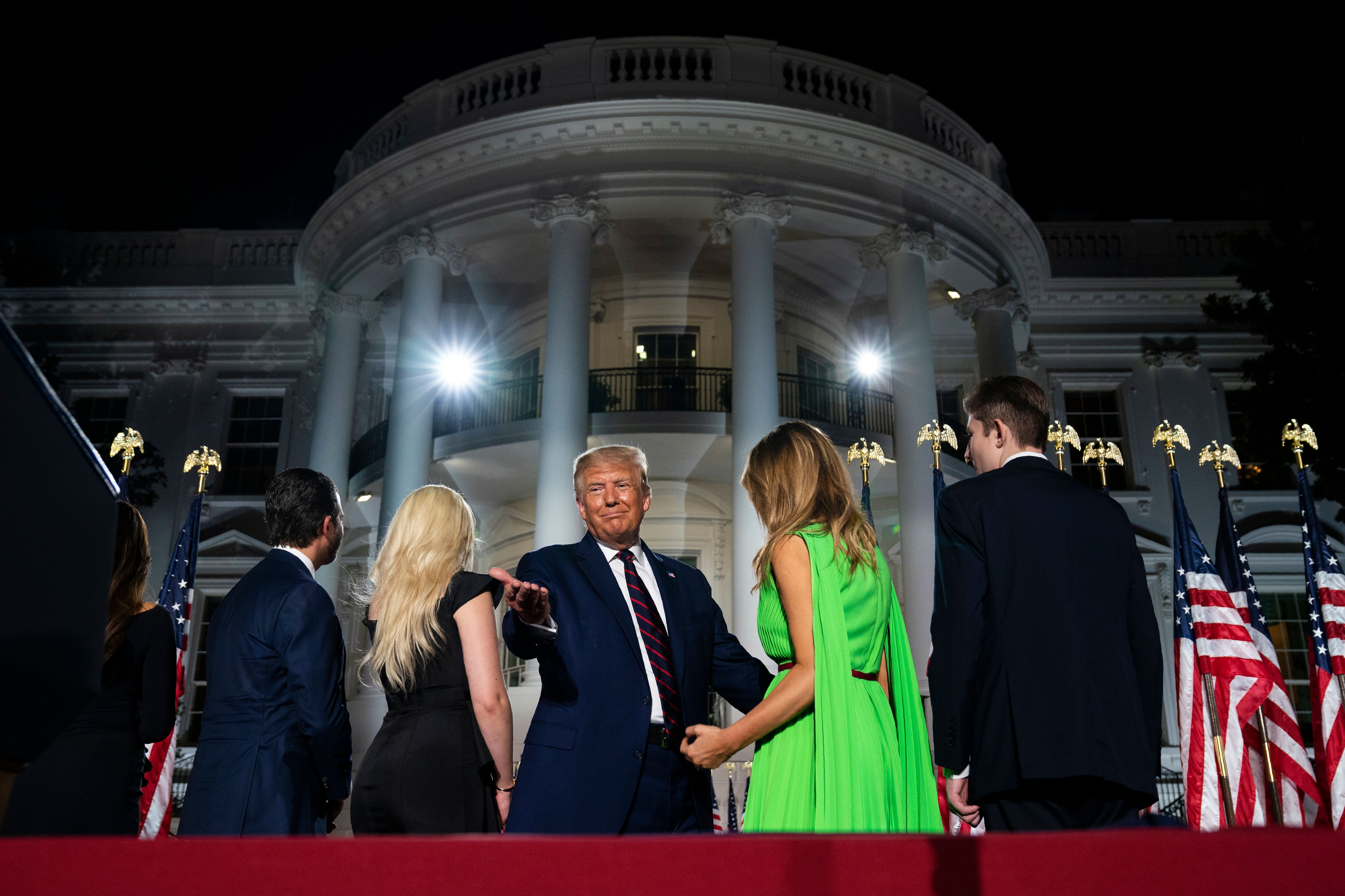 The president and his family standing before the White House — a federal government building they used as a prop for hi