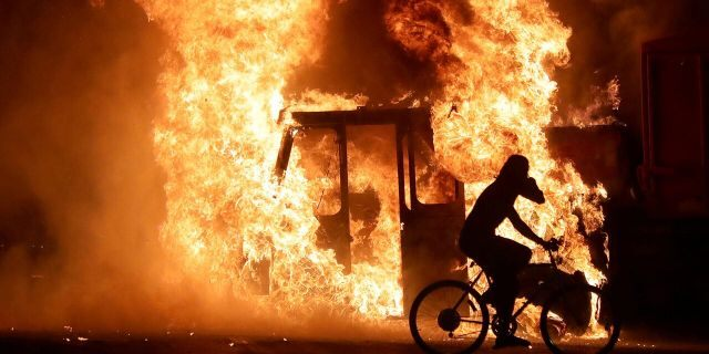 A man on a bike rides past a city truck on fire outside the Kenosha County Courthouse in Kenosha, Wisconsin, U.S., during protests following the police shooting of Black man Jacob Blake August 23, 2020. Picture taken August 23, 2020. Mike De Sisti/Milwaukee Journal Sentinel via USA TODAY via REUTERS MANDATORY CREDIT - RC2DKI99E9P9