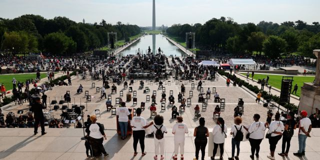 """Demonstrators gather at the Lincoln Memorial as final preparations are made for the March on Washington, Friday Aug. 28, 2020, at the Lincoln Memorial in Washington, on the 57th anniversary of the Rev. Martin Luther King Jr.'s """"I Have A Dream"""" speech. (Olivier Douliery/Pool via AP)"""