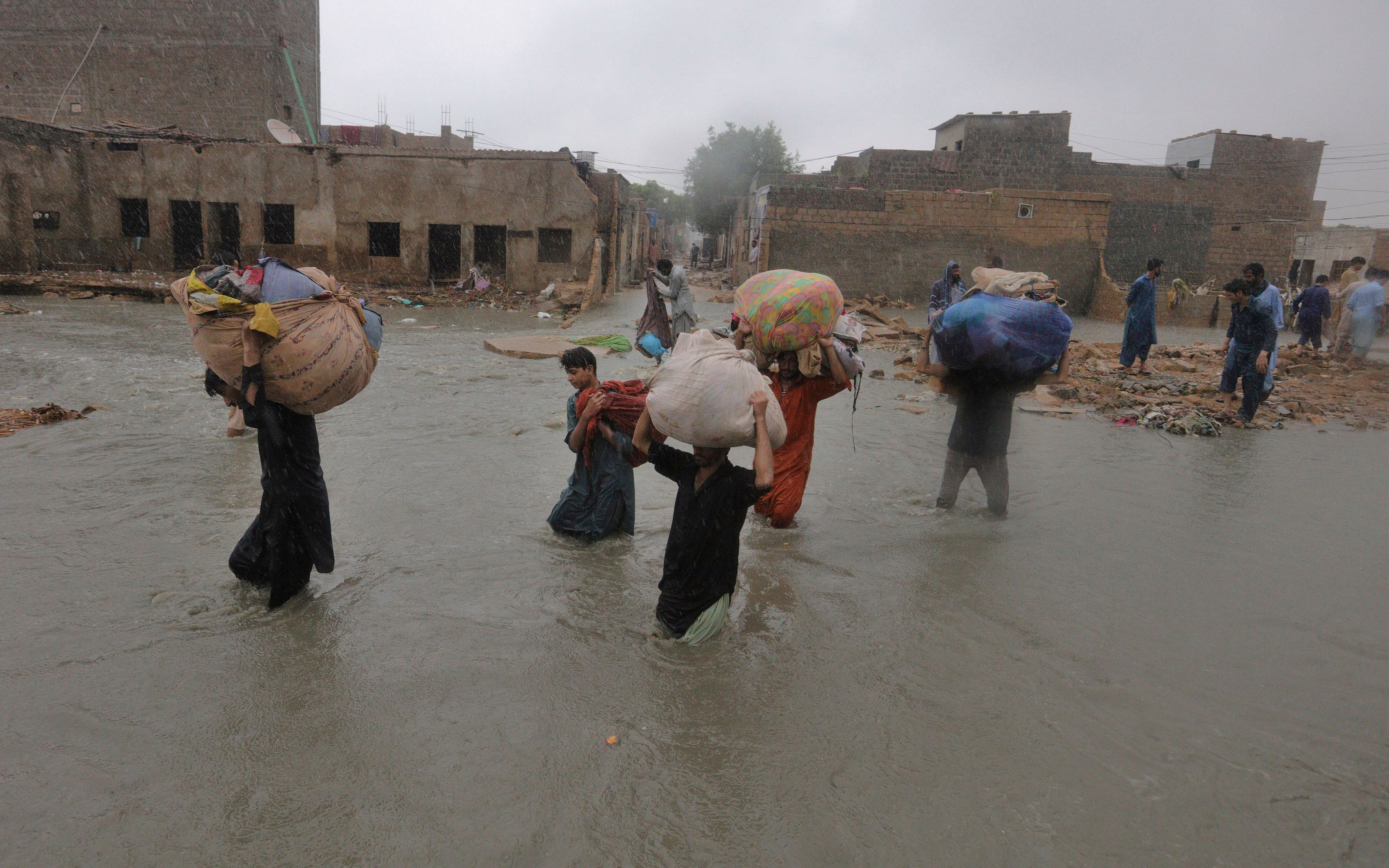 Local residents carry salvaged belongings as they wade through a flooded area during a heavy monsoon rain in Yar Mohammad vil