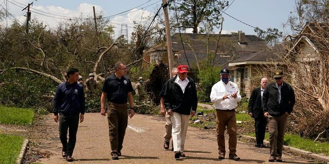 President Donald Trump talks with Louisiana Gov. John Bel Edwards, in white short, as he tours damage from Hurricane Laura, Aug. 29, in Lake Charles, La. (AP Photo/Alex Brandon)
