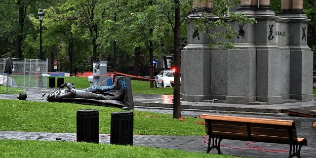 """A statue of the first Canadian Prime Minister John A. Macdonald lies on the ground, with the statue's head a few meters away, at Canada Park in central Montreal on August 29, 2020, after it was pulled down by anti-racism protesters during a demonstration calling for the defunding of the police. - Macdonald's government has been accused of seeking to assimilate indigenous peoples through forcible enrollment in residential schools, for example, that led to a loss of language and culture -- described in a 2015 reconciliation commission report as """"cultural genocide."""" (Photo by Eric THOMAS / AFP) (Photo by ERIC THOMAS/AFP via Getty Images)"""