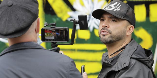 In this June 15, 2020, file photo, Joey Gibson, right, founder of the right-wing group Patriot Prayer, takes part in a livestream video broadcast, inside what has been named the Capitol Hill Occupied Protest zone in Seattle. (AP Photo/Ted S. Warren, File)