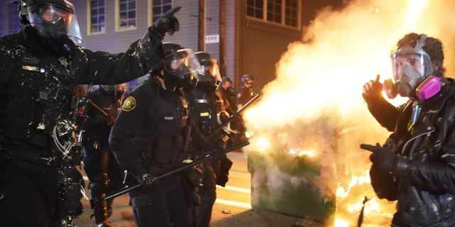 Portland police officers push protesters past a dumpster fire during a dispersal from in front of the Immigration and Customs Enforcement (ICE) detention facility in the early morning on August 21, 2020 in Portland, Oregon. (Photo by Nathan Howard/Getty Images)