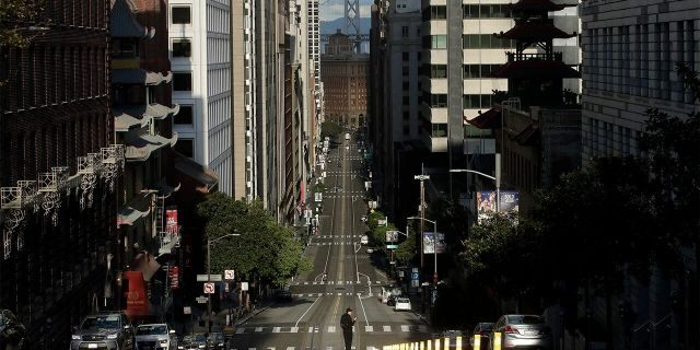 A man stands in the middle of a cable car tracks on a near empty California Street in San Francisco, Saturday, March 21, 2020. Some 40 million Californians are coping with their first weekend under a statewide order requiring them to stay at home to help curb the spread of the coronavirus(AP Photo/Jeff Chiu)