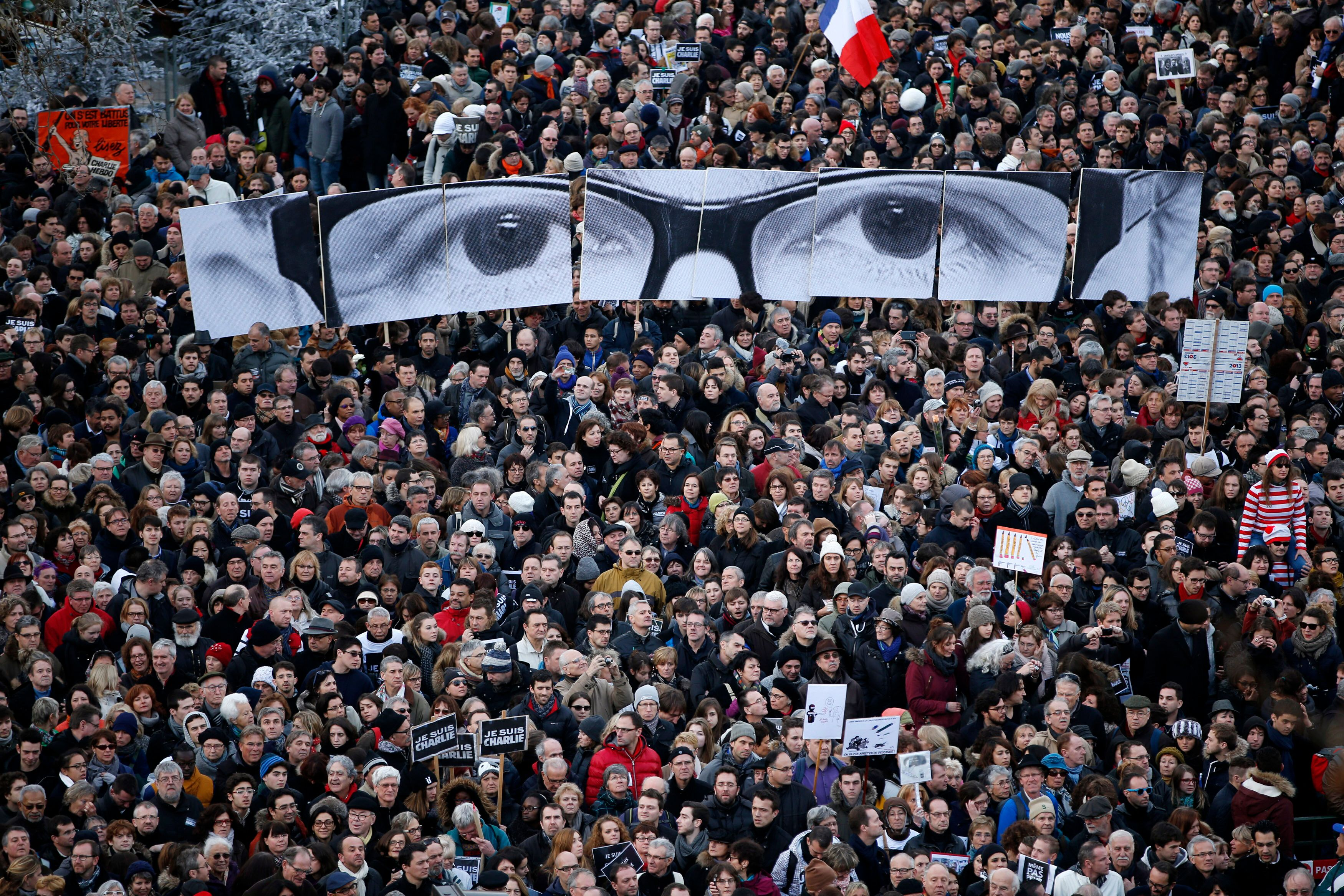 "People hold panels to create the eyes of late Charlie Hebdo editor Stephane Charbonnier, known as ""Charb,"" as hundreds of tho"