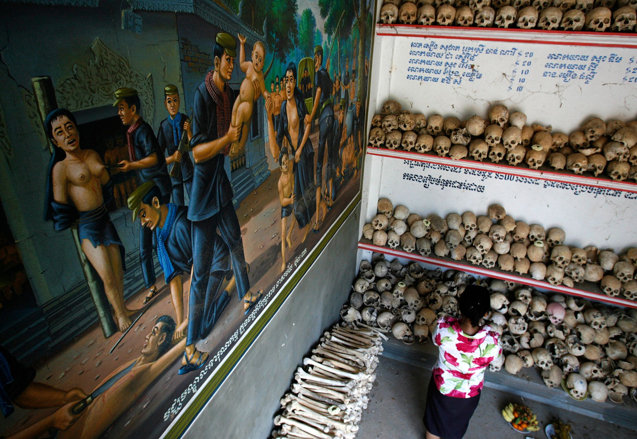 """A resident prays in front of skulls at a """"Killing Fields"""" memorial in Batey district in Kampong Cham province."""