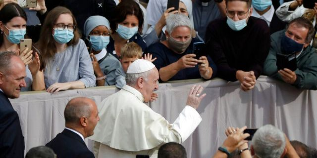 People wear face masks to prevent the spread of COVID-19 while Pope Francis waves as he arrives for his first general audience. (AP Photo/Andrew Medichini)