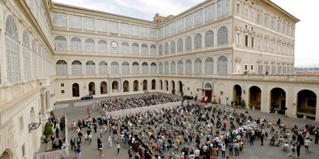 Faithful listen to Pope Francis, the white figure sitting at center right, during his general audience Wednesday at the San Damaso courtyard, at the Vatican, the first since February when the coronavirus pandemic began. (AP Photo/Andrew Medichini)