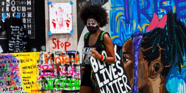 A marcher walks past banners and signs at Black Lives Matter Plaza near the White House in Washington, Aug. 28, 2020. (AP Photo/Manuel Balce Ceneta)