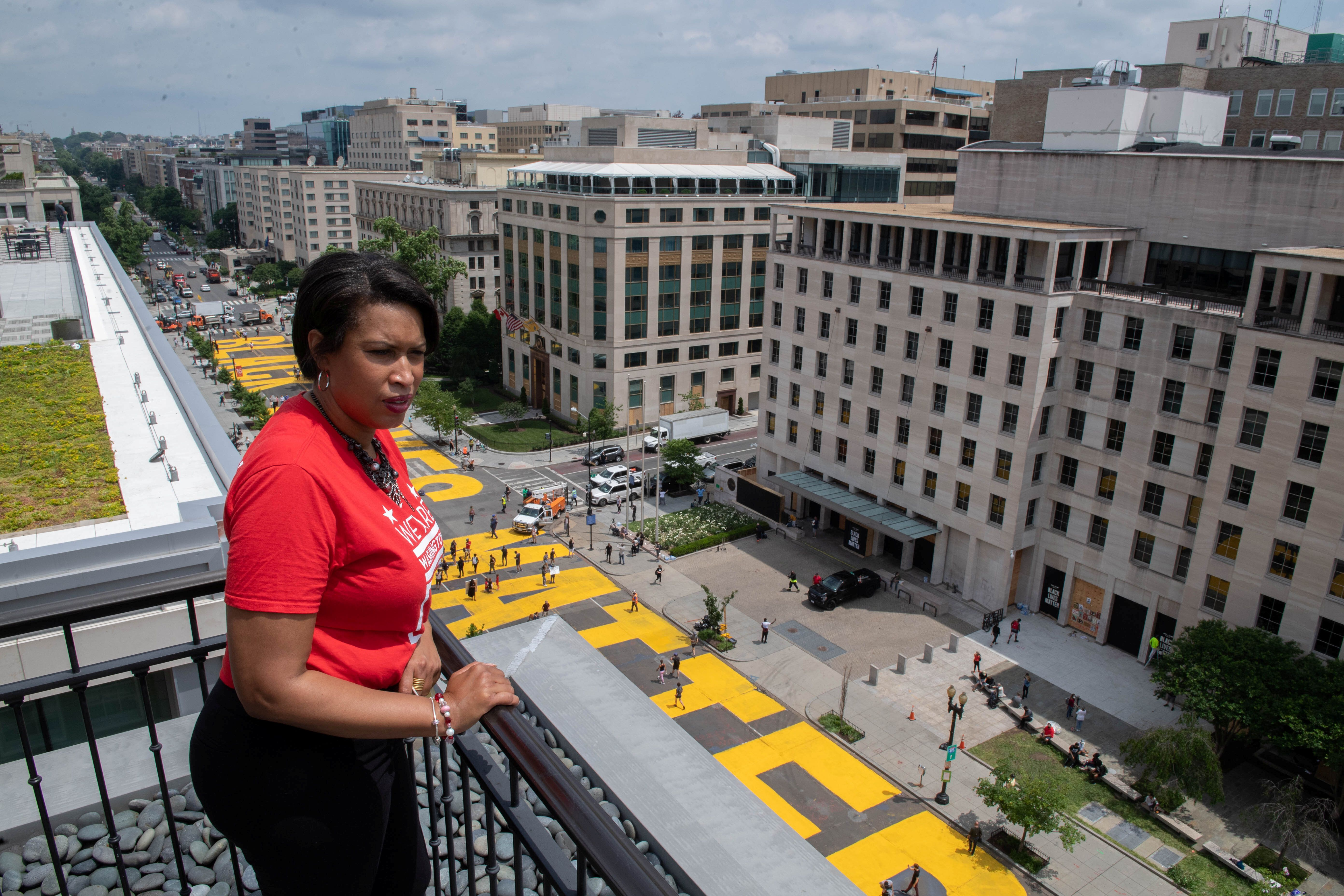 Mayor Muriel Bowser looks out over a Black Lives Matter sign that was painted during anti-racism protests in Washington, D.C.