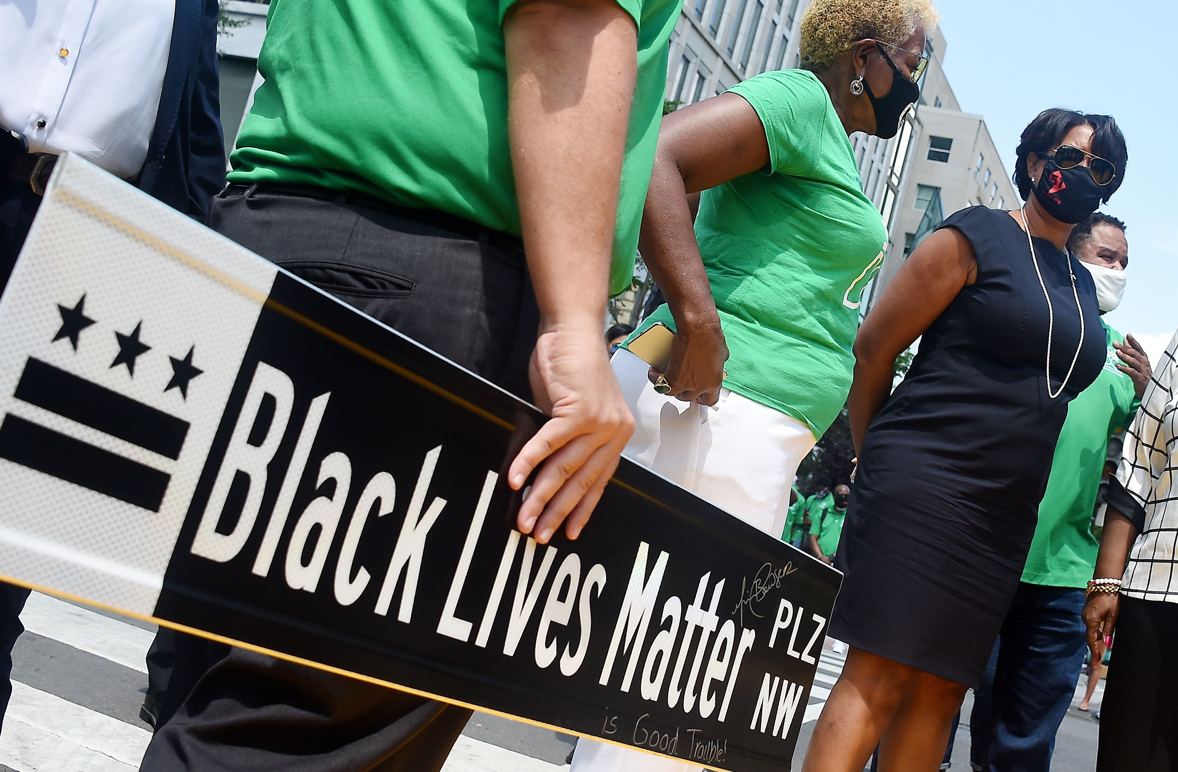 Mayor Muriel Bowser waits at Black Lives Matter Plaza to watch the funeral procession for Congressman and civil rights leader