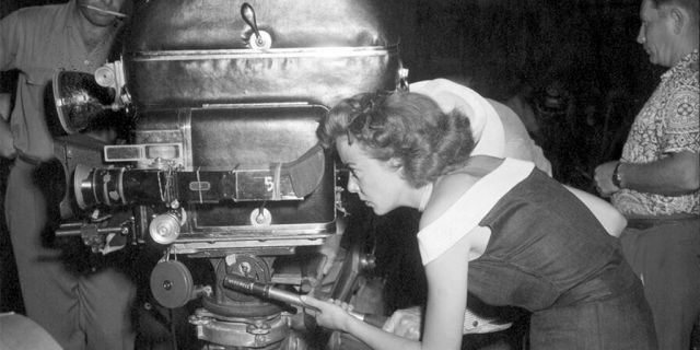 Ida Lupino directs one of the scenes from her film 'Mother of a Champion.' She is shown peering through the movie camera. Undated photograph.