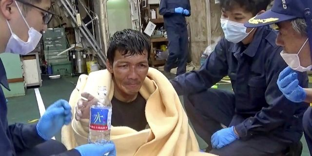 In this image made from video released by the 10th Regional Japan Coast Guard Headquarters, a rescued crew member of a Panamanian cargo ship takes a bottle of water as he speaks to Japanese Coast Guard members off the Amami Oshima, Japan Wednesday, Sept. 2, 2020. Japanese rescuers have safely plucked the crew member from the sea while searching for the cargo ship carrying more than 40 crew and thousands of cows went missing after sending a distress call off the southern Japanese island. (The 10th Regional Japan Coast Guard Headquarters via AP)