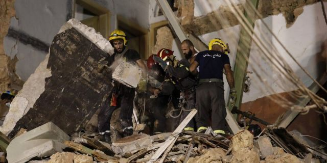 Rescuers search a building that collapsed in last month's massive explosion that hit the seaport of Beirut, after getting signals there may be a survivor under the rubble in Beirut, Lebanon, Early Friday, Sept. 4, 2020. A pulsing signal was detected Thursday from under the rubble of a Beirut building that collapsed during the horrific port explosion in the Lebanese capital last month, raising hopes there may be a survivor still buried there. (AP Photo/Hussein Malla)
