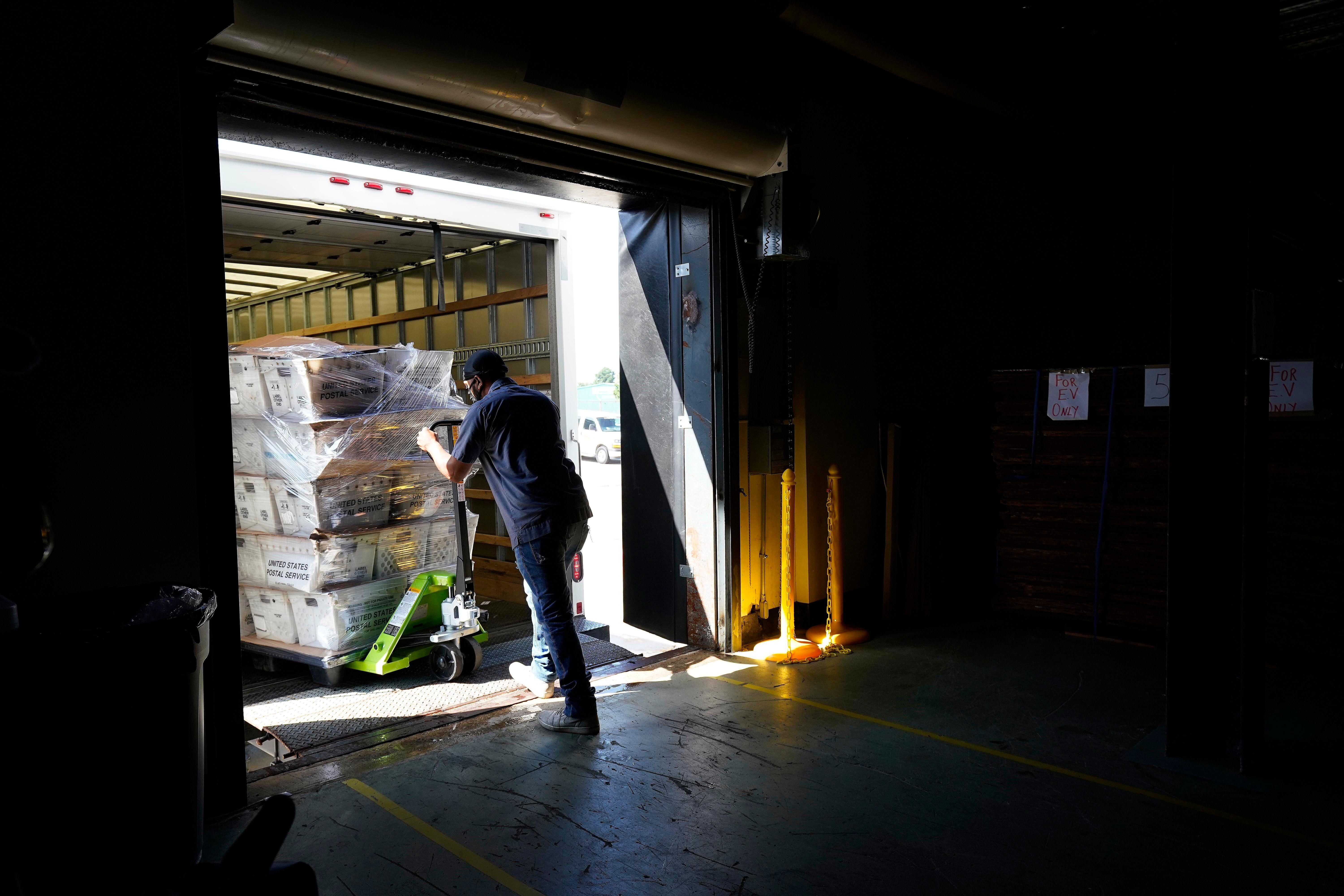 A load of absentee ballots is loaded onto a truck for mailing at the Wake County Board of Elections in North Carolina Thursda
